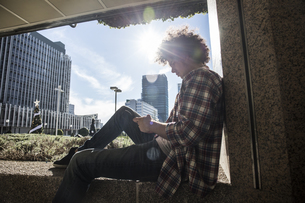 Young man sitting on wall in backlight looking at cell phoneの写真素材 [FYI04334023]