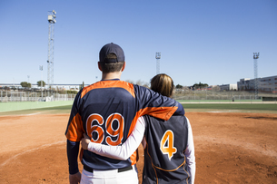 Rear view of male and female baseball player embracing on aの写真素材 [FYI04334029]
