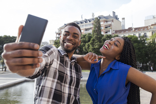 Portrait of happy young couple taking selfie with cell phoneの写真素材 [FYI04334036]