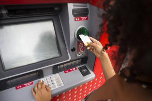 Woman pushing credit card at cash dispenserの写真素材 [FYI04334043]