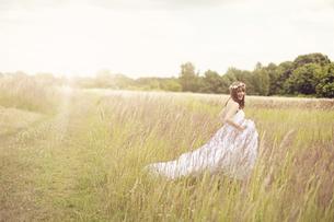 Happy bride wearing white wedding dress walking on a meadowの写真素材 [FYI04334044]