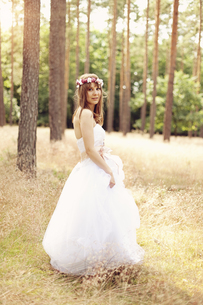 Bride wearing white wedding dress and flowers walking on a mの写真素材 [FYI04334046]