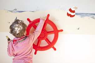 Toddler playing with red wheel fixed on a wallの写真素材 [FYI04334047]