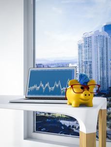 Happy piggy bank in front of laptop showing stock-market priのイラスト素材 [FYI04334092]
