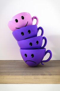 Stack of three smiling and one unhappy cupsのイラスト素材 [FYI04334094]