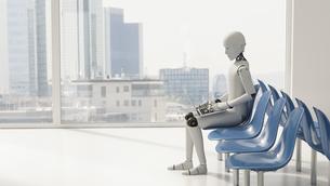 Robot sitting in waiting area, using laptopのイラスト素材 [FYI04334178]