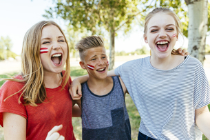 Austria, three teenagers with national colors painted on theの写真素材 [FYI04334249]