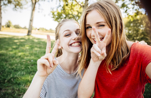 Two playful teenage girls making victory signの写真素材 [FYI04334251]