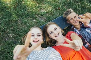 Three happy teenage friends lying on skateboard in meadow maの写真素材 [FYI04334254]
