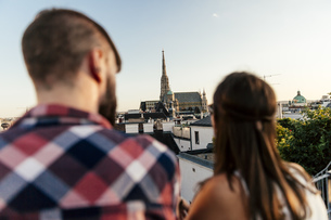 Austria, Vienna, back view of young couple on roof terrace lの写真素材 [FYI04334262]