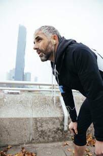 Austria, Vienna, exhausted athlete wearing earphonesの写真素材 [FYI04334267]