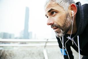 Austria, Vienna, exhausted athlete wearing earphonesの写真素材 [FYI04334268]