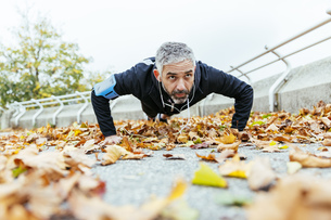 Man doing pushups surrounded by autumn leavesの写真素材 [FYI04334270]