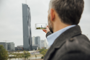 Austria, Vienna, businessman taking a picture of DC Towers wの写真素材 [FYI04334277]