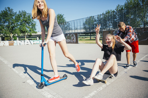 Three playful teenage friends with scooter and skateboardの写真素材 [FYI04334285]