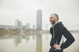 Austria, Vienna, portrait of smiling jogger with earphones iの写真素材 [FYI04334292]