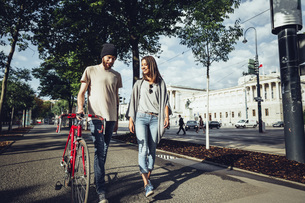 Austria, Vienna, young couple with bicycle in front of Parliの写真素材 [FYI04334295]