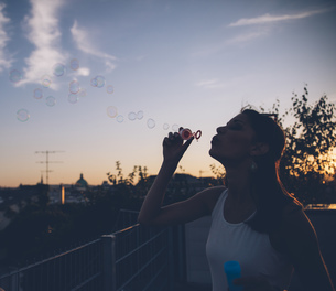 Young woman blowing soap bubbles on roof terrace in the evenの写真素材 [FYI04334299]