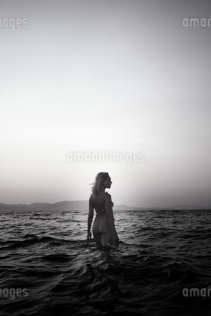 Naked young woman walking in the sea by twilightの写真素材 [FYI04334309]