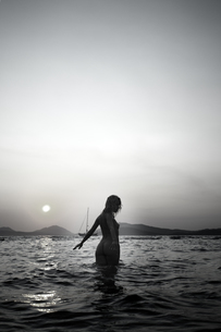 Naked young woman walking in the sea by twilightの写真素材 [FYI04334310]