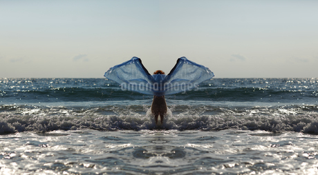 Silhouette of young woman in front of the sea holding blue cの写真素材 [FYI04334315]