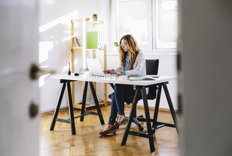 Young woman working with laptop at home officeの写真素材 [FYI04334346]