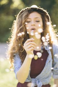 Young woman blowing dandelionの写真素材 [FYI04334349]