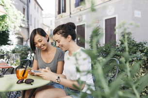 Italy, Padua, two young women checking their cell phones atの写真素材 [FYI04334354]