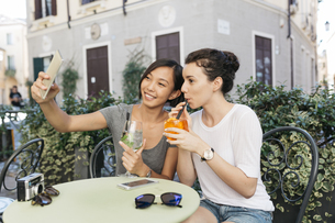 Italy, Padua, two young women taking selfie at sidewalk cafeの写真素材 [FYI04334355]