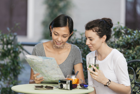 Two young women looking together at map at sidewalk cafeの写真素材 [FYI04334361]