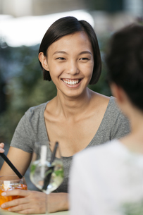 Portrait of happy young woman at sidewalk cafe with her frieの写真素材 [FYI04334362]