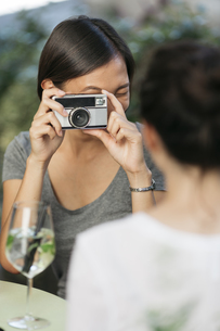 Young woman taking picture of her friend with camera at sideの写真素材 [FYI04334363]