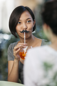 Portrait of young woman with toy moustache and cocktail at sの写真素材 [FYI04334364]