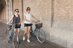 Two young women pushing their bikesの写真素材 [FYI04334365]