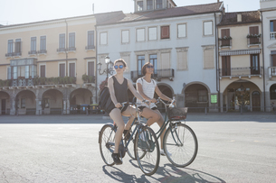 Italy, Padua, two young tourists riding bicycleの写真素材 [FYI04334371]