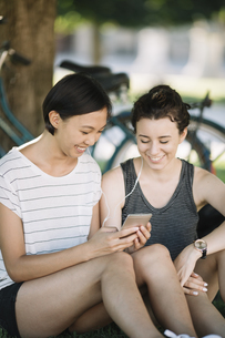 Two friends sitting in city park listening music together wiの写真素材 [FYI04334383]