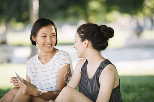 Two friends sitting in city park listening music together wiの写真素材 [FYI04334384]