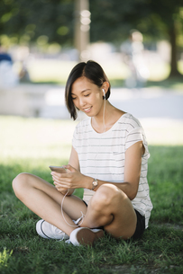 Smiling young woman sitting on a meadow listening music withの写真素材 [FYI04334385]