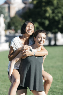 Young woman giving her friend a piggyback ride in the parkの写真素材 [FYI04334386]