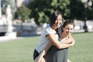 Young woman giving her friend a piggyback ride in the parkの写真素材 [FYI04334387]