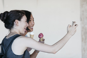 Two young women with ice cream cones taking selfie with smarの写真素材 [FYI04334395]