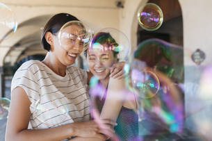 Two young women playing with soap bubblesの写真素材 [FYI04334402]