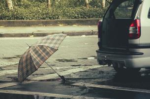 Brazil, Sao Paulo, Umbrella and car on the streetの写真素材 [FYI04334547]
