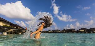 Maldives, Young woman splashing wet hair in lagoonの写真素材 [FYI04334570]