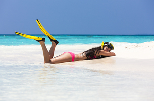 Maldives,Young woman lying in beachの写真素材 [FYI04334571]