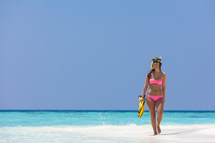 Maldives,Young woman walking on beachの写真素材 [FYI04334573]