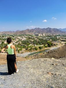 Oman, Dhakiliya, young woman looking to Bahla, Fort Bahal inの写真素材 [FYI04334693]