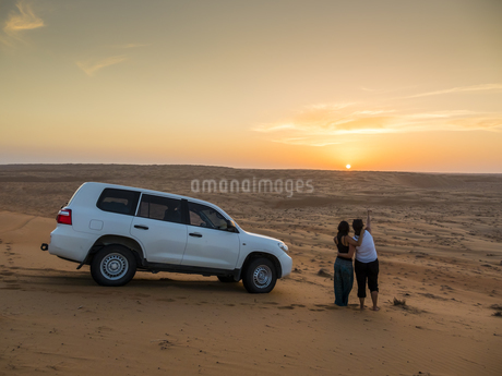 Oman, Al Raka, two young women standing besides off-road vehの写真素材 [FYI04334702]