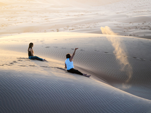 Oman, Al Raka, two young women sitting on a dune in Rimal Alの写真素材 [FYI04334703]