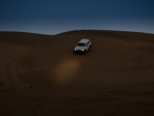Oman, Al Raka, off-road vehicle parking on dune in Rimal Alの写真素材 [FYI04334704]